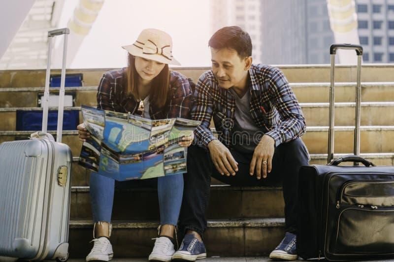 Los viajeros de los pares, leyeron el mapa para planear viaje en la plataforma i imagenes de archivo