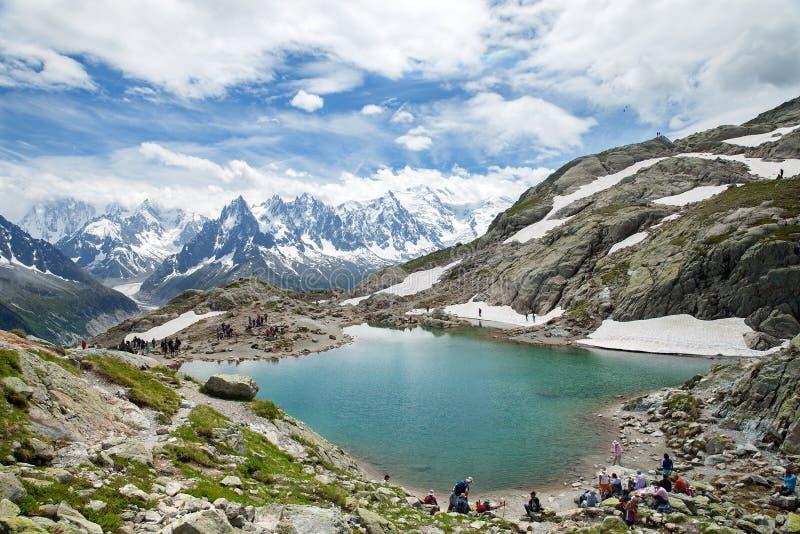 Los viajeros descansan sobre el borde del lago de la montaña, Chamonix fotos de archivo libres de regalías