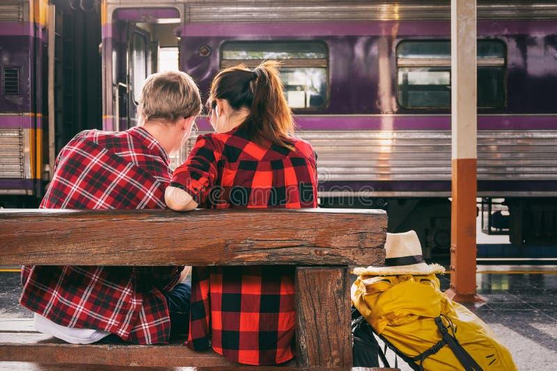 Los viajeros jovenes felicesdel couplejuntos de vacaciones se sientan en el t fotos de archivo