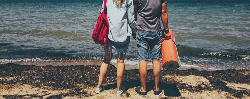 Los viajeros jovenes irreconocibles hombre y mujer de los pares que se colocan en la costa y que disfrutan de viaje del viaje de  imágenes de archivo libres de regalías