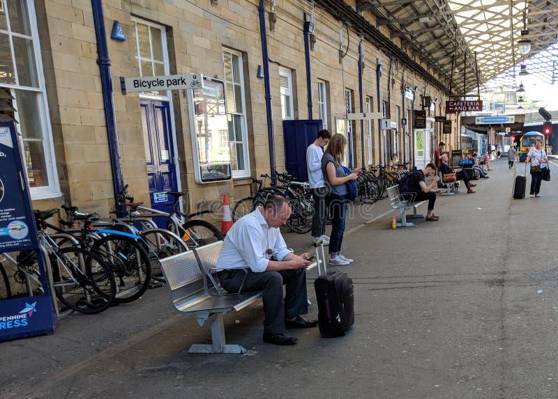Los viajeros utilizan los teléfonos móviles en la estación de Huddersfield fotos de archivo libres de regalías