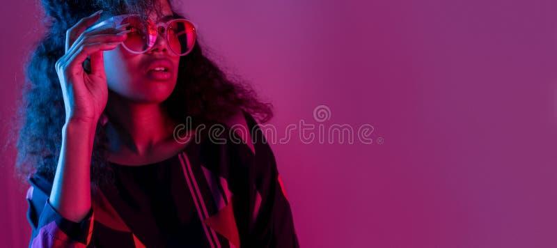 Los vidrios africanos jovenes del desgaste de la muchacha de la moda miran la cámara aislada en la pared púrpura imagen de archivo libre de regalías