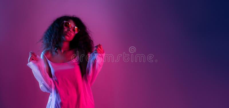 Los vidrios africanos jovenes del desgaste de la muchacha de la moda miran la cámara aislada en la pared púrpura fotografía de archivo libre de regalías