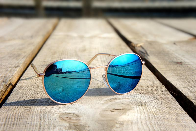 Los vidrios con los vidrios azules en el sol mienten en un resto de madera del piso foto de archivo libre de regalías