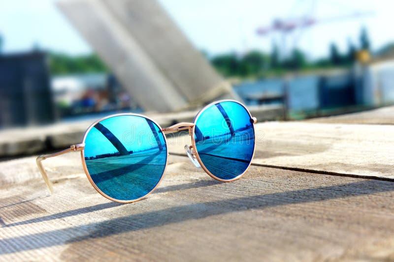 Los vidrios con los vidrios azules en el sol mienten en un resto de madera del piso fotografía de archivo