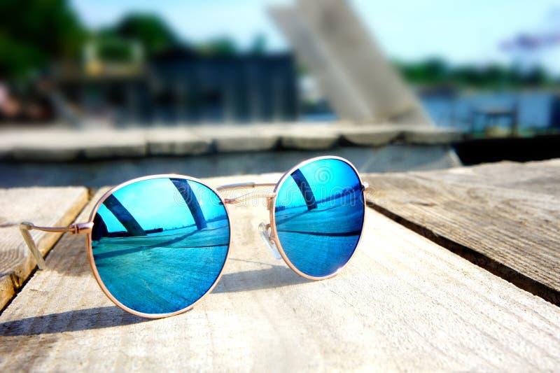 Los vidrios con los vidrios azules en el sol mienten en un resto de madera del piso imágenes de archivo libres de regalías