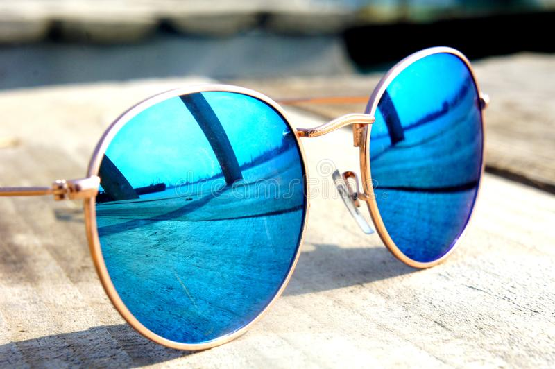 Los vidrios con los vidrios azules en el sol mienten en un viaje de madera del resto del piso reflejado en un vidrio fotos de archivo