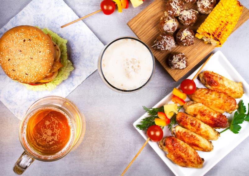 Los vidrios de cerveza con las alas de pollo, hamburguesa, bolas de carne, asaron a la parrilla maíz y verduras Mordeduras de la  imagen de archivo