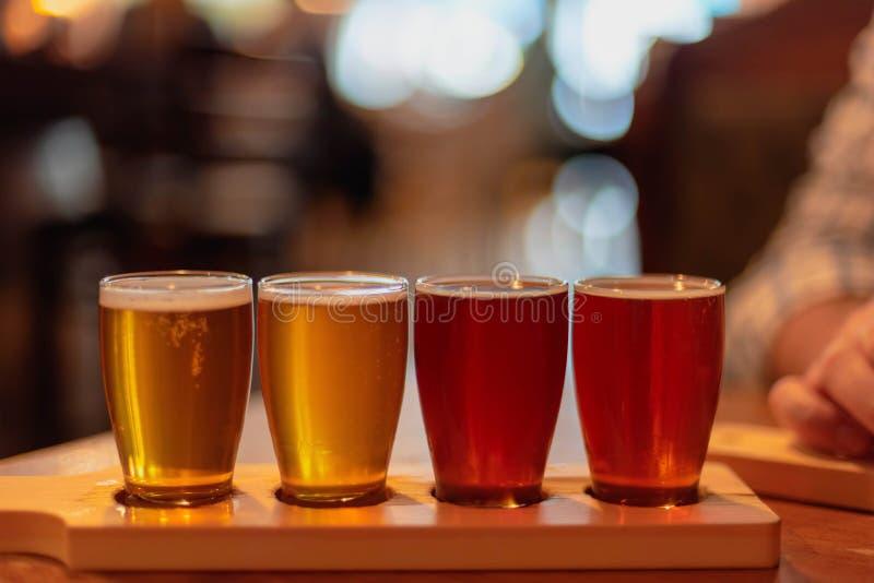 Los vidrios de cerveza del arte se alinearon en la tabla fotos de archivo