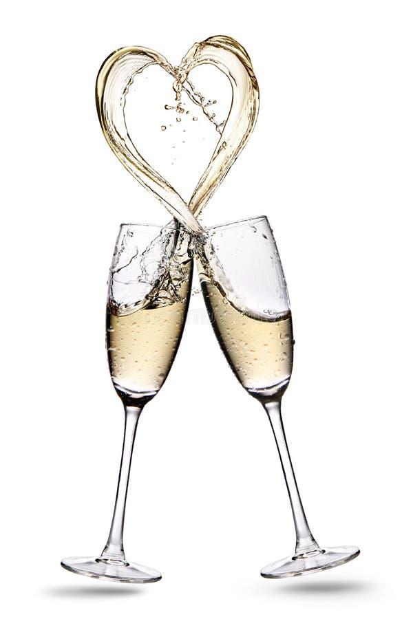 Los vidrios de champán con forma del corazón salpican aislado en un fondo blanco imagenes de archivo