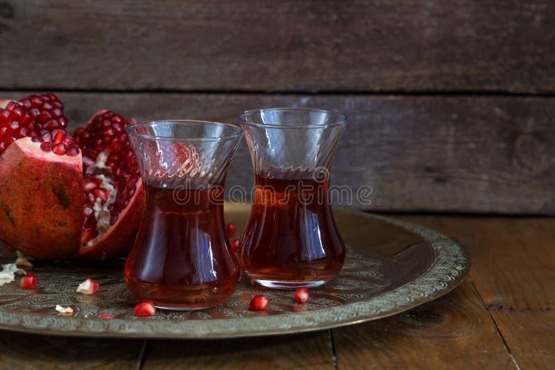 Los vidrios de jugo de la granada con la granada fresca dan fruto en la tabla de madera Vitaminas y minerales Bebida sana imagen de archivo