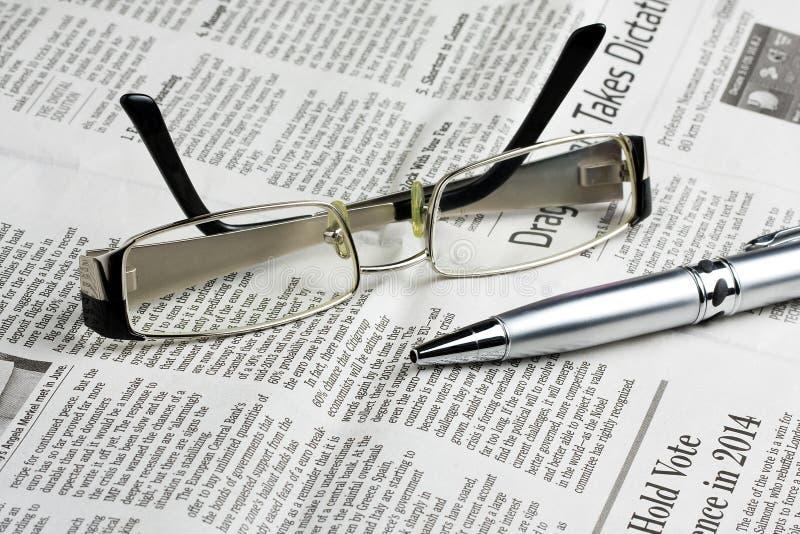 Vidrios de lectura en el periódico con la pluma fotografía de archivo