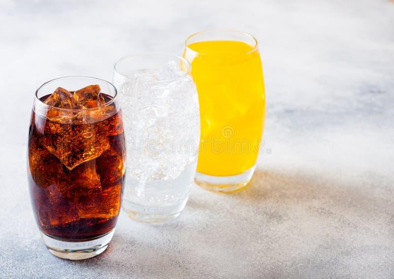 Los vidrios de soda beben con los cubos y las burbujas de hielo en el fondo de piedra de la tabla de cocina Cola y soda anaranjad fotografía de archivo