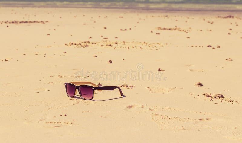 Los vidrios de Sun mienten en una playa cerca del mar fotografía de archivo