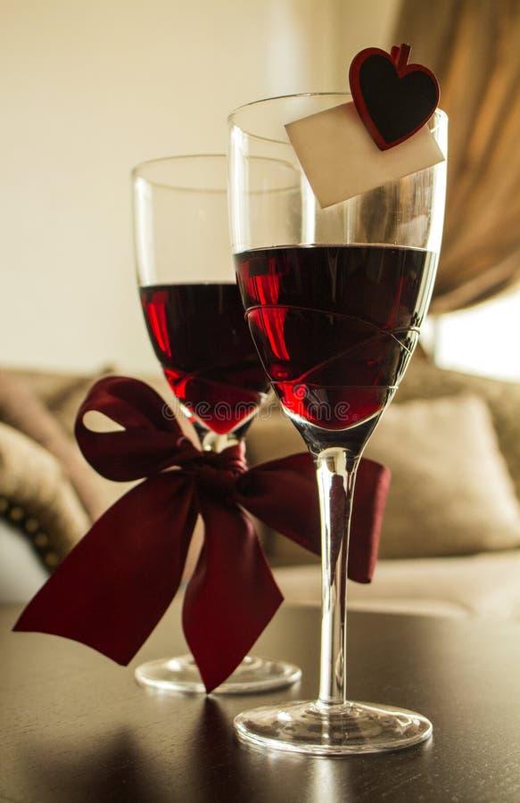Los vidrios de vino rojo con las decoraciones Borgoña arquean, perno del corazón, tarjeta de felicitación imagen de archivo