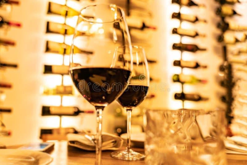 Los vidrios de vino tinto en un tablón de madera con las botellas defocused atormentan en el fondo fotografía de archivo