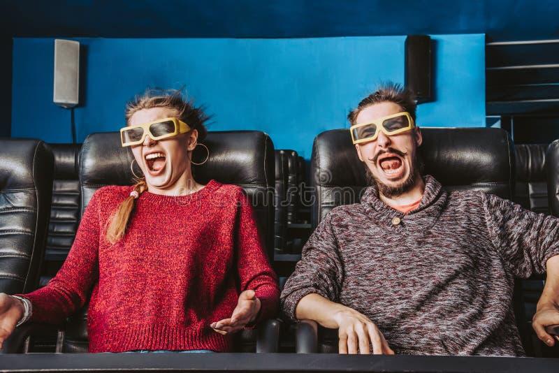 Los vidrios del individuo y de la muchacha 3d son muy preocupantes mientras que miran una película foto de archivo libre de regalías