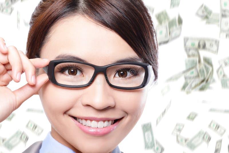 Los vidrios del ojo del tacto de la mujer de negocios con el dinero llueven imagenes de archivo