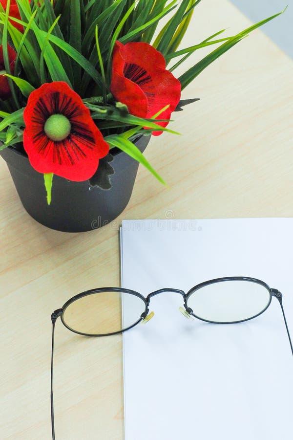 Los vidrios en el papel en blanco al lado del pote de la flor falsa pusieron la etiqueta de madera imagen de archivo