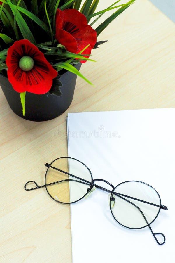 Los vidrios en el papel en blanco al lado del pote de la flor falsa pusieron la etiqueta de madera imagenes de archivo