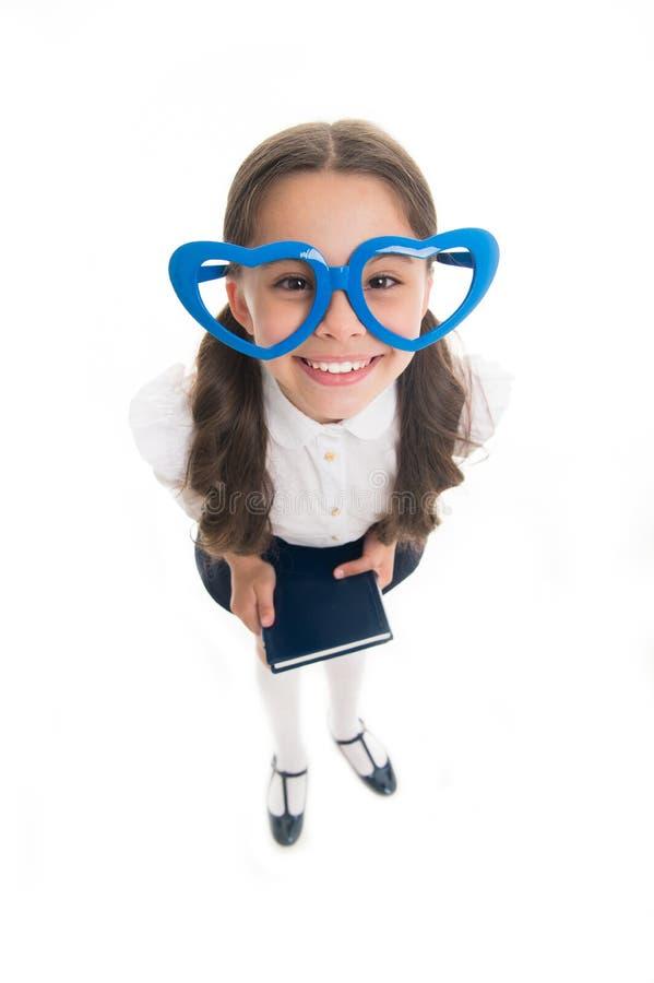 Los vidrios en forma de corazón grandes lindos de la muchacha aislaron el fondo blanco La muchacha del niño que el uniforme escol foto de archivo