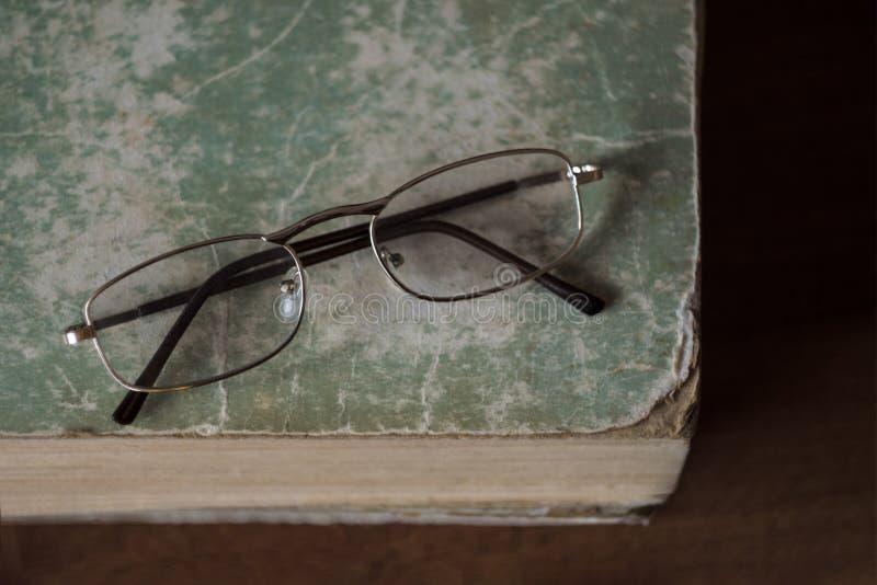Los vidrios mienten en un libro viejo con los bordes rasgados con una cubierta lamentable El concepto de aprendizaje, de lectura  fotos de archivo
