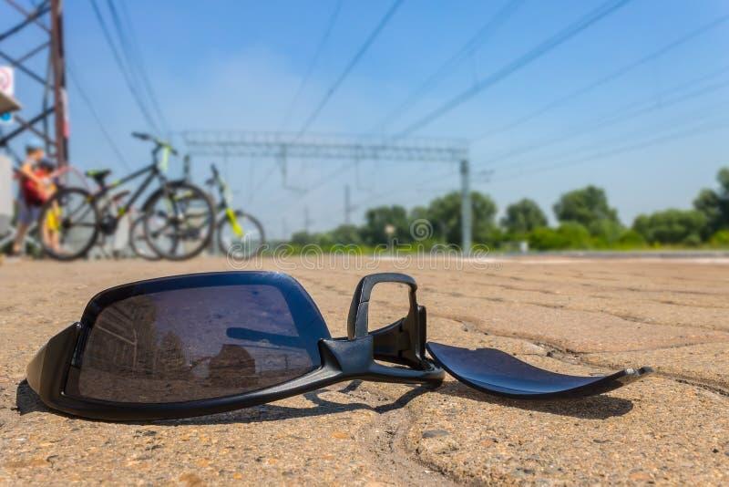 Los vidrios negros rotos y perdidos mienten en el camino contra el contexto de ciclistas fotos de archivo libres de regalías