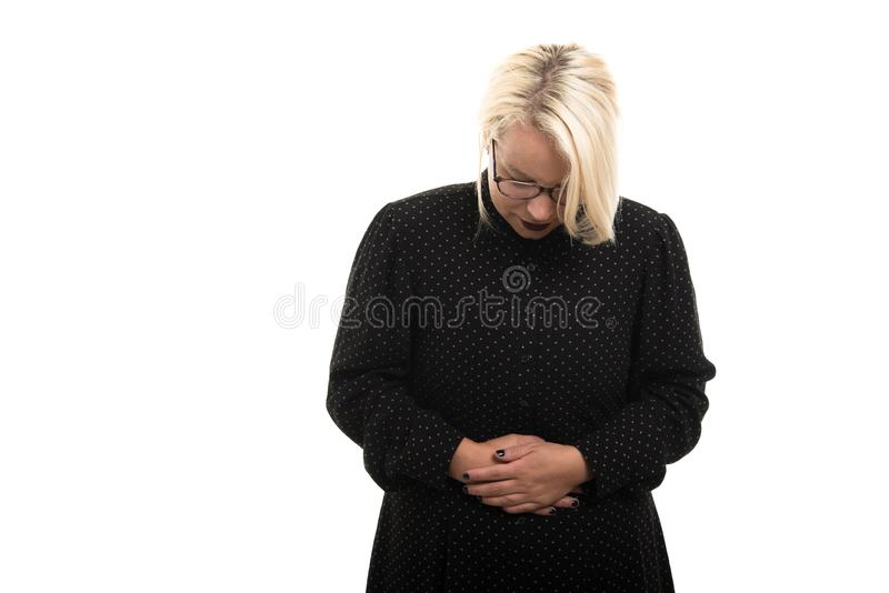 Los vidrios que llevan rubios del profesor de sexo femenino que muestran el dolor de estómago duelen g foto de archivo libre de regalías
