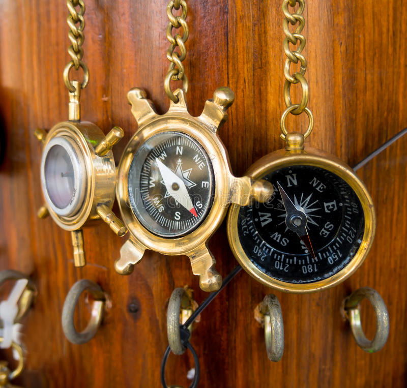 Los viejos compases de bronce están colgando en una cadena en una pared de madera fotos de archivo