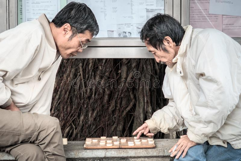 Los viejos hombres chinos jubilados juegan a ajedrez chino en la calle de Hong Kong fotografía de archivo