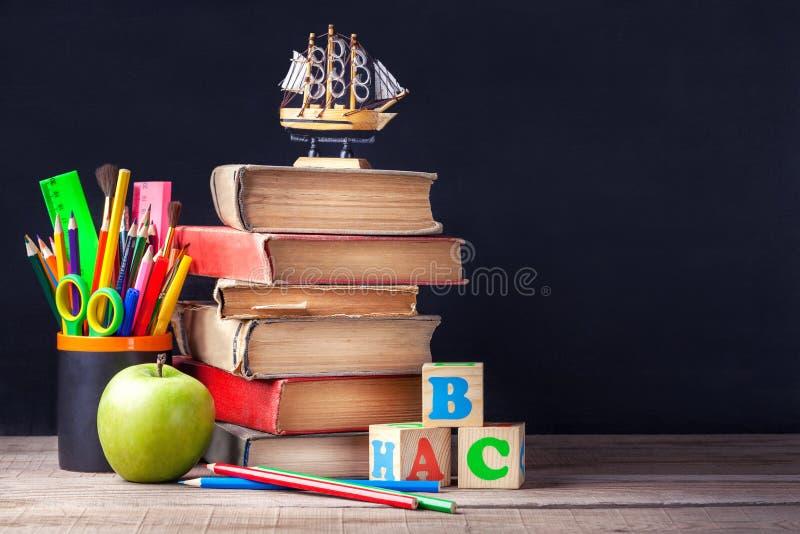 Los viejos libros de texto y fuentes de escuela están en la tabla de madera rústica en un fondo del tablero de tiza negro imagenes de archivo