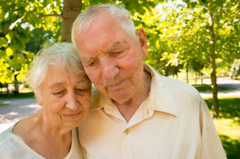 Los viejos pares tristes en el verano en un paseo imagenes de archivo