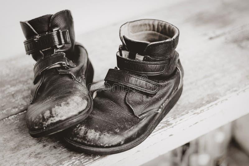 Los viejos zapatos de cuero negro Shabby están sobre la mesa de madera imagenes de archivo