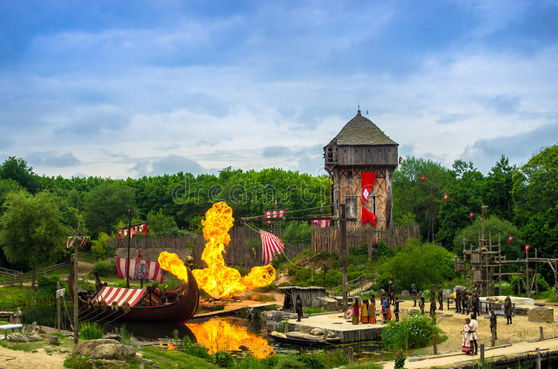 Los Vikingos y sus lanchas que atacan un pequeño pueblo en una demostración impresionante en el parque temático de Puy du fou, Fr imagenes de archivo