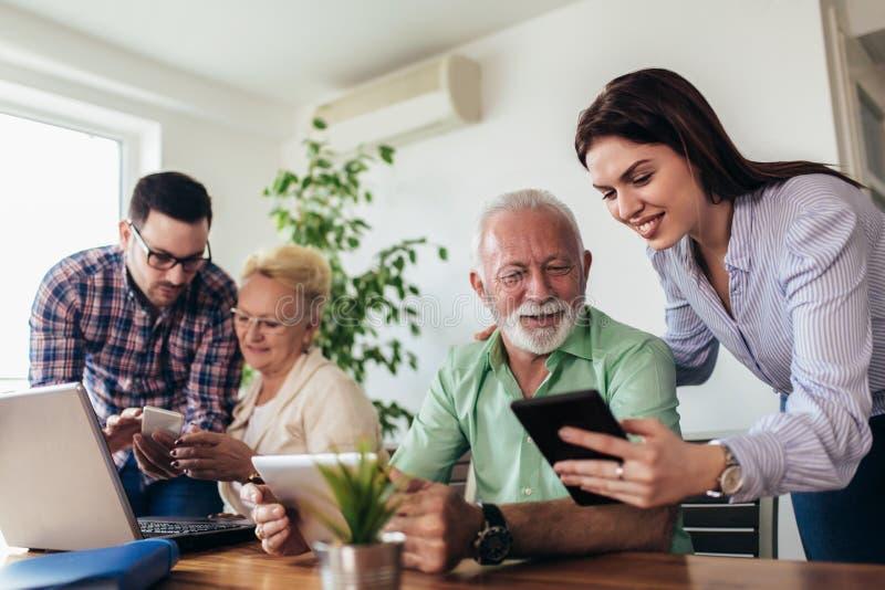 Los voluntarios ayudan a gente mayor en el ordenador Gente joven que da la introducción mayor de la gente a Internet fotografía de archivo