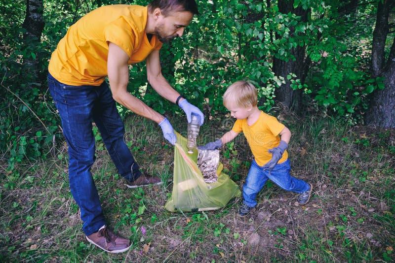 Los voluntarios del padre y del hijo recogen la basura plástica en la naturaleza para ahorrar el ambiente de la contaminación imagen de archivo
