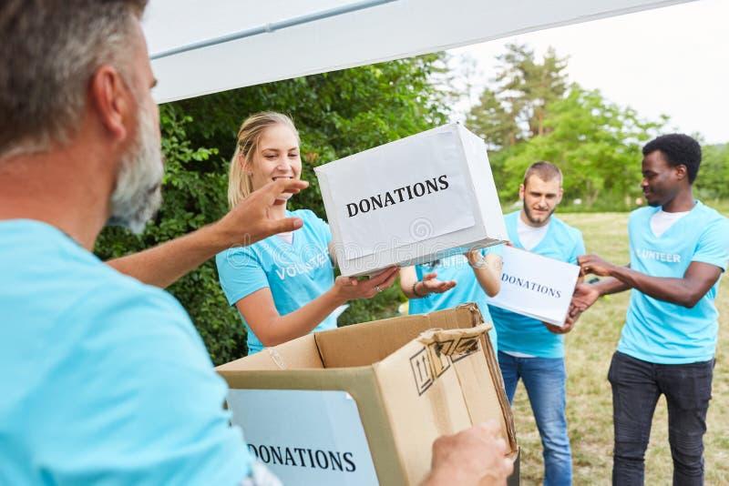 Los voluntarios en trabajo voluntario recogen las donaciones para el club imágenes de archivo libres de regalías
