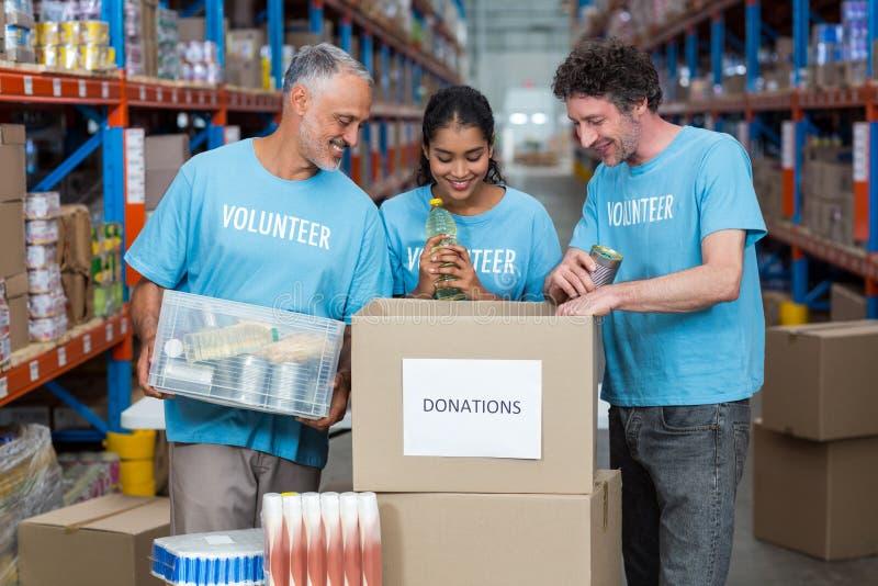 Los voluntarios felices están mirando dentro de una caja de las donaciones imagenes de archivo