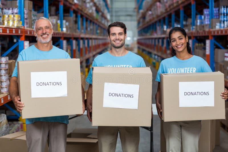 Los voluntarios felices están sosteniendo las cajas de las donaciones y están mirando la cámara foto de archivo libre de regalías