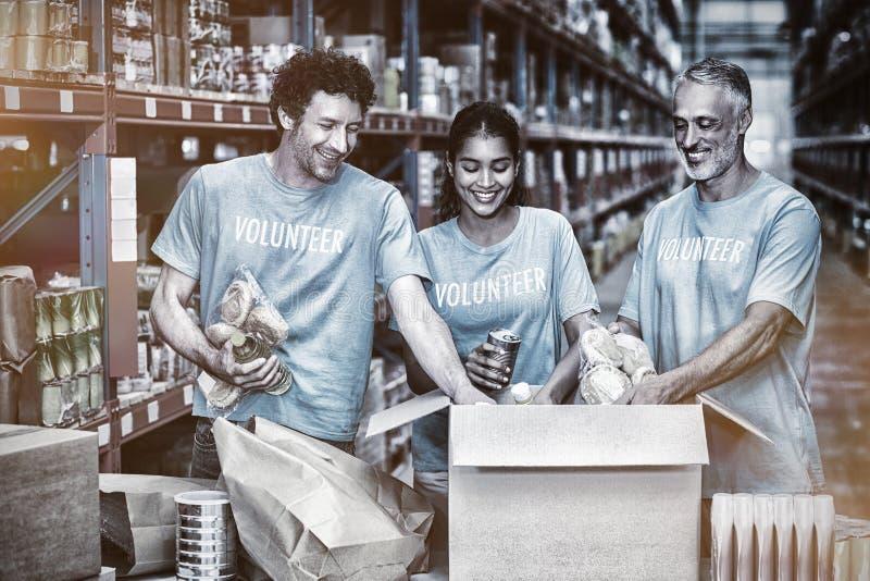 Los voluntarios felices ponen en orden algunas mercancías en caja de cartón imágenes de archivo libres de regalías