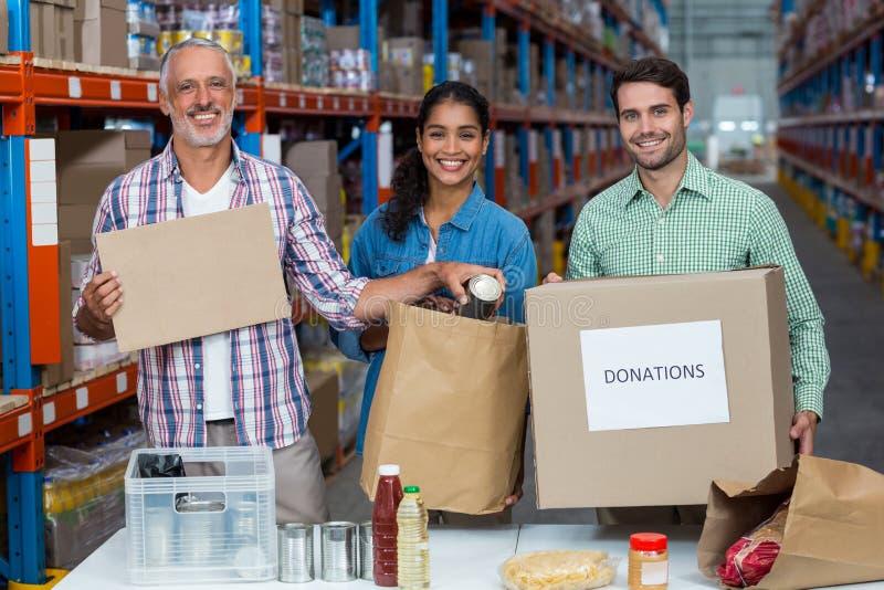 Los voluntarios felices son de presentación y sonrientes durante trabajo foto de archivo libre de regalías
