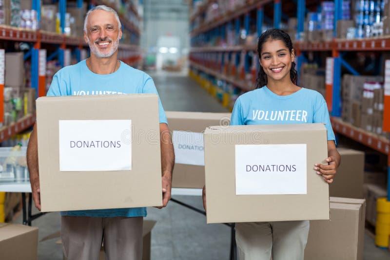 Los voluntarios felices son sonrientes y que sostienen las cajas de las donaciones fotografía de archivo