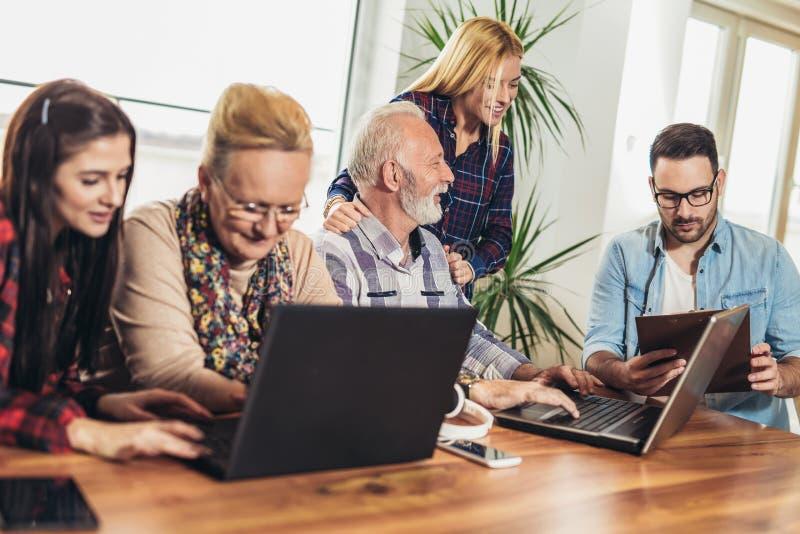 Los voluntarios jovenes ayudan a gente mayor en el ordenador imagen de archivo