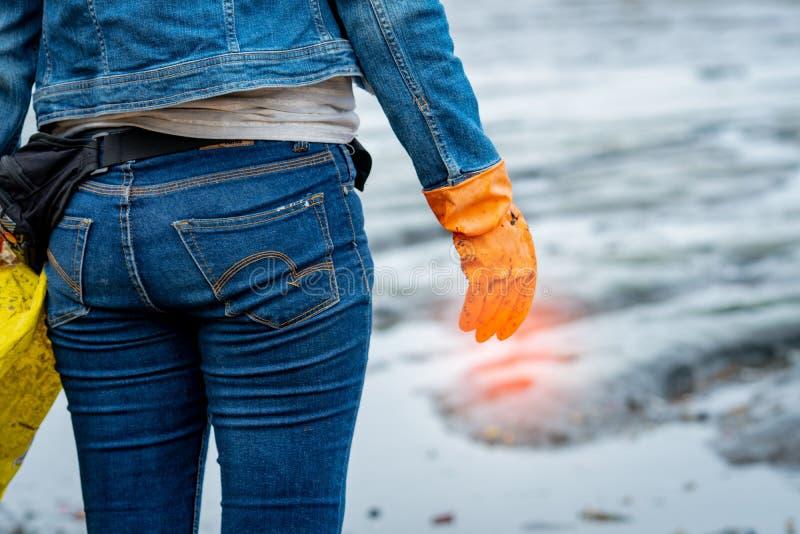 Los voluntarios llevan vaqueros y las camisas con mangas largas y llevan guantes de goma anaranjados para recoger la basura en la fotografía de archivo libre de regalías