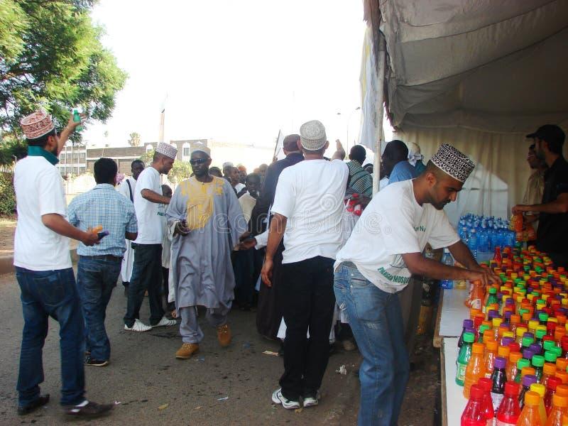 Los voluntarios musulmanes distribuyen el jugo foto de archivo