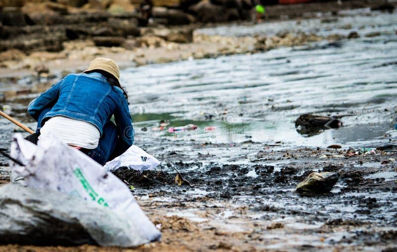 Los voluntarios se sientan y cogiendo la basura en la playa Limpiador que recoge la basura en la playa del mar adentro a la bolsa foto de archivo