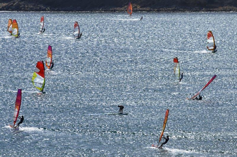 Los Windsurfers montan en las ondas brillantes del mar Mediterráneo hermoso foto de archivo libre de regalías