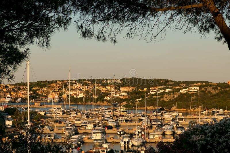 Los yates de lujo amarraron en un puerto de Oporto Cervo en la puesta del sol temprana, Cerdeña, Italia fotografía de archivo