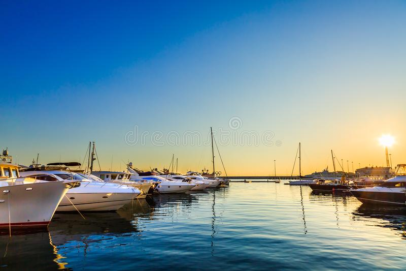 Los yates de lujo, la navegación y los barcos de motor atracaron en puerto marítimo en la puesta del sol Estacionamiento marino d foto de archivo