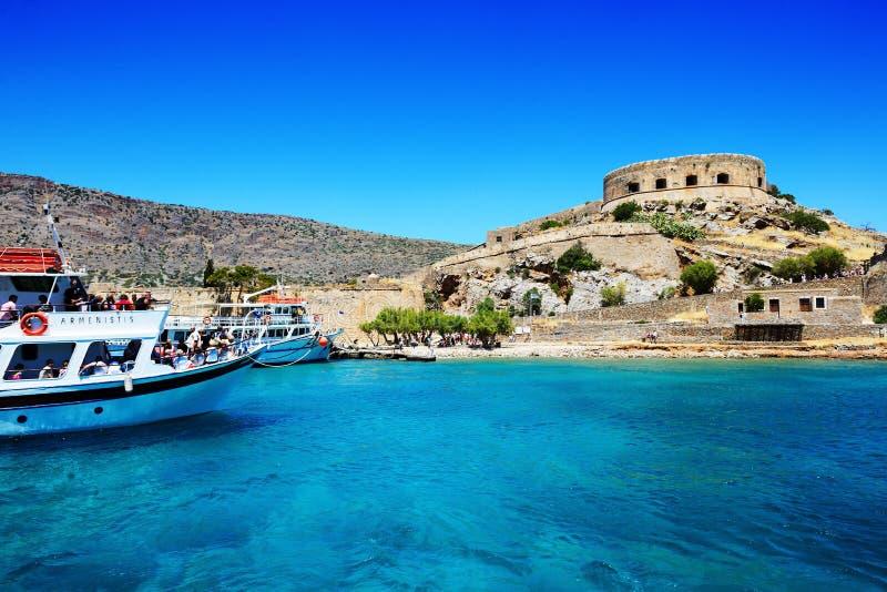 Los yates del motor con los turistas están cerca de isla de Spinalonga fotografía de archivo